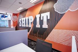 Mural naranja que dice ship it en una pared de la oficina de HubSpot en Singapur