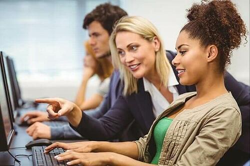 Profesora de marketing señala la pantalla de la computadora de una estudiante durante una lección sobre texto alternativo